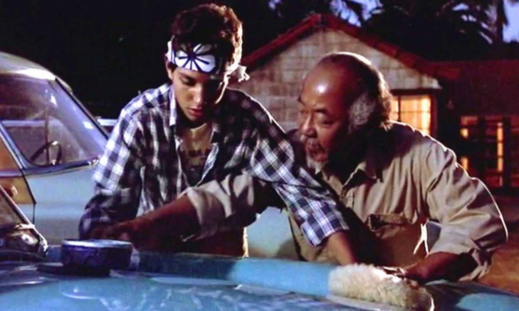 Photo of Karate Kid doing wax on, wax off with Mr Miyagi